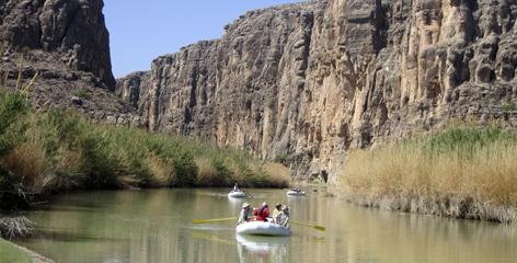 Rafts piloted by guides from Far Flung Outdoor Center of Terlingua, Texas, emerge from Heath Canyon, carved by the Rio Grande through Big Bend National Park, Texas.