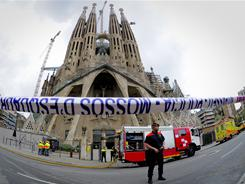 Firemen stand in front of the Sagrada Familia Basilica on Tuesday in Barcelona after a fire broke out inside. Tourists were evacuated but later allowed back inside.