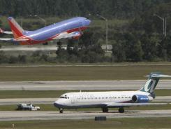 A Southwest jet takes off as an AirTran plane rolls to its gate at Orlando International.