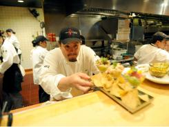 Sous chef Mark Segura sends out an order at Rick Bayless' Topolobampo restaurant in Chicago.