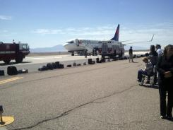 "A Delta Air Lines jet headed to San Diego from Detroit sits at a remote area of Albuquerque International Sunport on Sunday after the flight was diverted due to a ""potential security threat."""