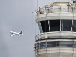 A passenger jet flies past the FAA control tower at Washington's Ronald Reagan National Airport in March.