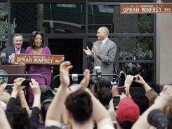 Talk-show host Oprah Winfrey is honored with a street named for her outside her Harpo Studios in Chicago by Chicago Mayor Richard M. Daley, left, and Bobby Ware, commissioner of the Chicago Department of Transportation on May 11.