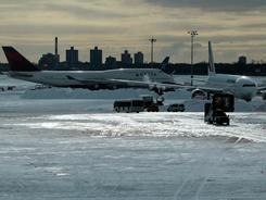 The snow-covered tarmac at Terminal 4 of John F. Kennedy International Airport is seen in December 28, 2010 in New York City. While booking flights through a tour operator can't prevent extreme weather situations from cutting into a trip and may be more costly, but that way the tour operator is responsible for getting you rebooked in case of flight cancellations.