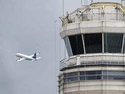 A passenger jet flies past the FAA control tower at Washington's Reagan National Airport.