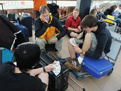Passengers at Hamburg's airport play cards after their flight to Rome was delayed on May 25, 2011.