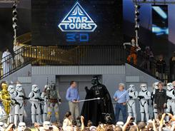 George Lucas joins Disney CEO Robert Iger, Darth Vader and other characters on stage at the reopening of the Star Tours ride at Walt Disney World.