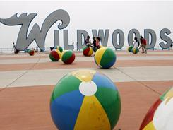 People mingle near the huge Wildwoods sign on the boardwalk in Wlidwood, N.J. The three-town resort is the winner of this year's Best Beaches contest.