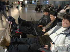Three travelers keep busy on their computers while waiting for their flight out of Logan Airport in Boston. Free Wi-Fi can hinder airport revenue since travelers aren't walking around spending money, one wireless provider says.