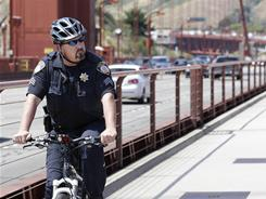 A Golden Gate Bridge Patrol officer patrols the bridge in San Francisco. As millions flock to summer vacations at national landmarks, the level of post-Sept. 11 security often depends on the symbolism.