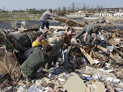 Rescue workers search tornado debris for a 16-month-old baby, May 24, in Joplin.