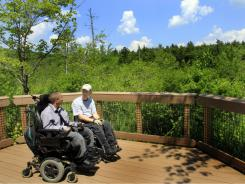 Chelsea Fernandes, left, and Mark Race take a break from exploring the woods at the Crotched Mountain Rehabilitation Center in Greenfield, N.H. The center offers over 2.5 miles of  privately funded trails designed to be easily accessible for people in wheelchairs and those who have difficulty walking.