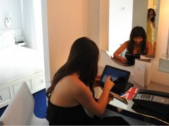 Seunghee Thomson checks the hotel iPad in the room she shares with her sister, Nabe Kim,  at the Mondrian SOHO Hotel in New York City.