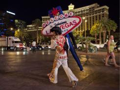 "Rodrigo Gonsalez walks along The Strip with a ""Welcome to Las Vegas"" sign as he finished up a night of impersonating Elvis, June 23, in Las Vegas. Gonsalez, a welder by trade, has turned to street performing in the absence of construction jobs in the city."