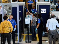 TSA agents screen passengers at Los Angeles International Airport.