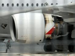 Emergency crews attend to an engine on a Qantas Airbus A380 aircraft, after it made an emergency landing, Nov. 4, 2010, at the Changi International airport in Singapore.