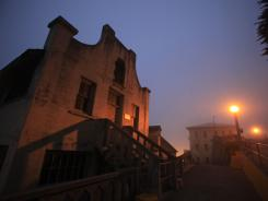 A military chapel at left is illuminated during a night tour on Alcatraz Island in San Francisco.