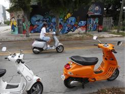 Jesse Bull, an economics professor at Florida International University, rides by during a two-hour graffiti tour given by Roam Rides in the Wynwood neighborhood of Miami.