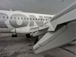 A wing of a Frontier Airlines plane shows dents from a hail storm in Denver on Thursday.