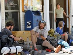 Postmistress Maie Beane chats with Appalachian Trail thru-hikers, from left, Greg Brown, and David Hyman, of Pleasantville, N.Y., and Madelyn Hoagland-Hanson, of Philadelphia, as they eat lunch outside the post office in Caratunk, Maine, July 28.