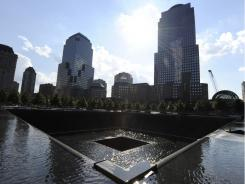 The National September 11 Memorial &amp; Museum at the site of the former World Trade Center complex features two waterfalls and reflecting pools set within the footprints of the north, shown here, and south towers of the World Trade Center.