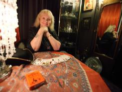 Willow Houston waits for clients in her tarot reading room in Salem, Mass. Salem, home to the infamous witch trials of the 17th century, sees its ties to witchcraft as a blessing and a curse.