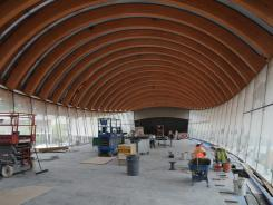 Construction workers work to finish the flooring in what will be the restaurant in one of the domed roof, glass-enclosed buildings at Crystal Bridges Museum.