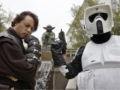 Matt Tolosa, left, dressed like the Star Wars movie character Anakin Skywalker, and his brother Dale Tolosa, right, dressed as a Stormtrooper, pose in front of a life-sized replica of Yoda at Lucasfilm Ltd. production studios in San Francisco.