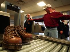 Dave Peterson, of Cedar Rapids, Iowa, is searched by airport security as his shoes roll off the conveyor belt of an X-ray machine at the Eastern Iowa Airport in Cedar Rapids.