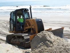 Beach Island, N.J.:  Lloyd Vosseller, a public-works employee in Harvey Cedars, shores up eroded dunes.