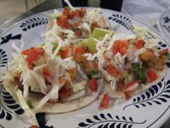 Baja Fish Tacos at La Gloria feature fried and breaded chunks of fresh fish, topped with cabbage and a chili cheese cream.