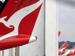 The tail of a Qantas plane pokes out of a hanger at Sydney Airport on Sunday.