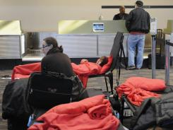 Stranded passengers rest on cots at Bradley International Airport in Windsor Locks, Conn., on Sunday.