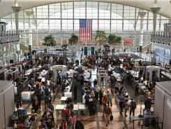 Passengers move through a main security checkpoint at the Denver International Airport in Denver, Colo., three days before Thanksgiving last year.