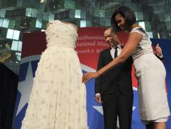 First lady Michelle Obama touches her 2009 inaugural gown as the dress designer, Jason Wu, looks on during a ceremony at the Smithsonian's National Museum of American History in Washington, D.C., in March 2010.