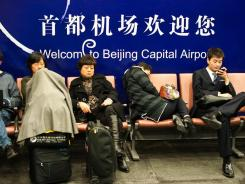 Fliers wait Oct. 30 at Beijing airport during delays due to severe smoggy weather.