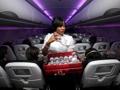 Something to drink?  Flight attendant Tasha Dunnigan serves passengers on a Virgin America flight.
