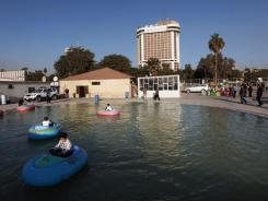 Baghdad's Ishtar Sheraton hotel stands in the background of this amusement park.