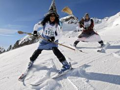 A group of skiers dressed as witches participate in the downhill race at Belalp-Blatten, Switzerland, as part of the annual event.