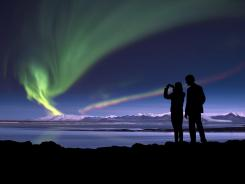 Tourists photograph Aurora Borealis over Vatnajokull ice cap, Iceland