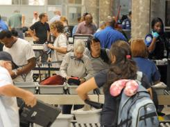 Passengers go through the TSA checkpoint Aug. 3 at Hartsfield-Jackson Atlanta International Airport.