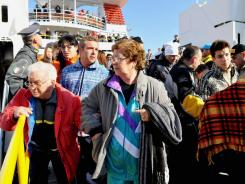 Crowds prepare to leave the island of Giglio, where passengers aboard the cruise ship Costa Concordia have been staying after the vessel ran aground on Friday.