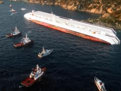 A handout aerial view taken and released Saturday by Italian Guardia de Finanza shows the Costa Concordia cruise ship after it ran aground and keeled over off the coast of Italy.