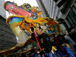 Neil Wu carries a dragon head as he marches with the San Francisco Police Lion Dance Team during the Chinese New Year Parade for the Year of the Rooster in San Francisco. The Year of the Dragon is approaching.