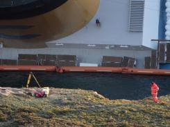 The cruise ship Costa Concordia remains off Italy on Tuesday. Divers exploded holes in the hull to search for missing passengers and crew.