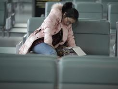 An airplane passenger watches a movie on her tablet device as she sits in the waiting hall at Hongqiao airport in Shanghai, China, on Jan. 3.