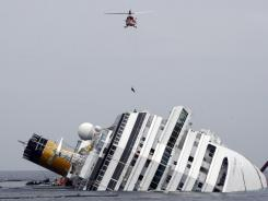An Italian firefighter is lowered from a helicopter onto the cruise ship Costa Concordia off Italy's coast Tuesday.