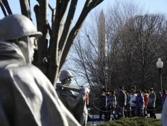 A Chinese tour group at the Korean War Veterans Memorial with the Washington Monument in the background.