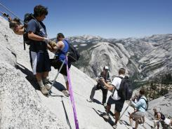 Climbers on the cable section of Half Dome negotiate the steep granite pitch in Yosemite National Park, Calif.