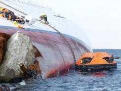 Italian firefighters work on the hull of the cruise ship Costa Concordia off Italy's coast on Sunday.